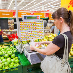 SAMARA RUSSIA - JUNE 13 2015: Young woman weighing bananas on electronic scales in produce department of the Auchan store