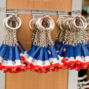 PARIS - SEPTEMBER 21: Key rings shaped as the most famous french landmark Eiffel tower in colors of the french flag in a souvenir shop on September 21 2013 in Paris France.