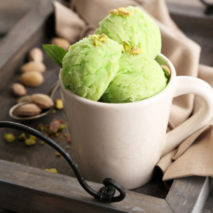 Tasty pistachio ice cream in cup on wooden table