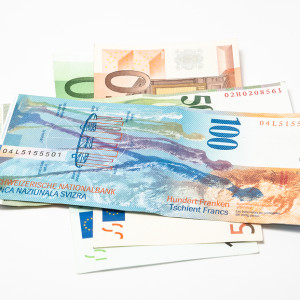 swiss frank banknotes laying over euro over white