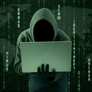 Hacker typing on a laptop with binary code background