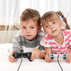 Happy children - girl and boy playing a video game