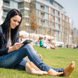 Young woman reading book on electronic book-reader outdoor